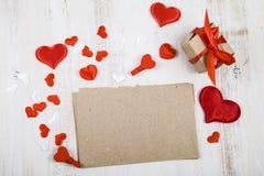 Papier, Geschenk und Herzen auf einem hölzernen Hintergrund Grußkartenesprit Stockfotos