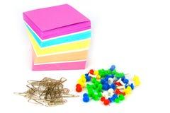 Papier, goupilles et tas colorés de note des agrafes en métal d'isolement sur un fond blanc Photo stock