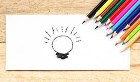 Papier, idée d'ampoule et crayons de couleur sur la table en bois Photographie stock
