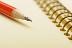 Papier jaune de cahier et crayon rouge Images stock