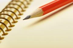 Papier jaune de cahier et crayon rouge Image stock