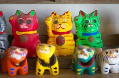 Papier mache beckoing cat or fortune cat or figure of a cat with one paw raised or maneki neko. Chiba,Japan-February 19, 2019: Papier mache beckoing cat or royalty free stock photos
