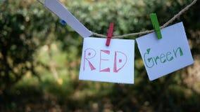 Papier mit Handschriftswortfarben, blaues, rotes, grünes Hängen an einem Seil mit hölzernem Clip und im Wind auf grüner Natur ent stock video