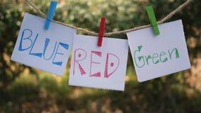 Papier mit Handschriftswortfarben, blaues, rotes, grünes Hängen an einem Seil mit hölzernem Clip und im Wind auf grüner Natur ent stock video footage