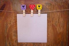 Papier mit Wäscheklammern mit den Herzen, die von einem Seil hängen stockfotos