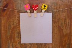 Papier mit Wäscheklammern mit heartson ein hölzerner Hintergrund Lizenzfreie Stockbilder