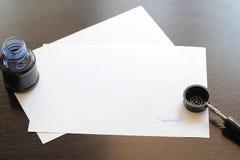 Papier mit Zeichentinte und Füllfederhalter auf hölzernem Schreibtisch Lizenzfreies Stockfoto
