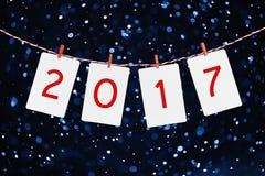 Papier- oder Fotorahmen mit 2017 Zahlen, die auf dem roten gestreiften Seil hängen Schneefallhintergrund, Design des neuen Jahres Stockbilder