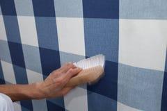 Papier peint accrochant de décorateur avec l'outil de travail dans le mouvement Photographie stock