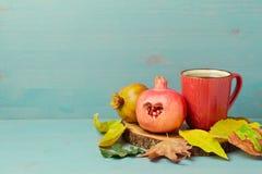 Papier peint d'automne avec la tasse de thé, la grenade et les feuilles rouges de chute Image stock