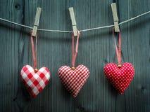 Papier peint de Saint-Valentin - coeurs de textile accrochant sur la corde Photographie stock