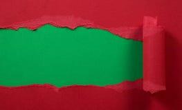 Papier rouge déchiré avec le fond vert Photo stock
