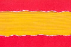 Papier rouge déchiré avec un fond en bois jaune Image libre de droits