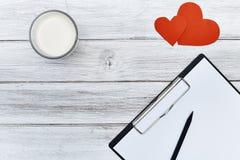 Papier rouge de coeurs du crayon deux de bloc-notes avec du lait Photographie stock