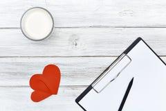 Papier rouge de coeurs du crayon deux de bloc-notes avec du lait Photographie stock libre de droits