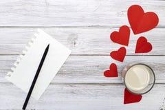 Papier rouge de coeurs du crayon deux de bloc-notes avec du lait Photo stock