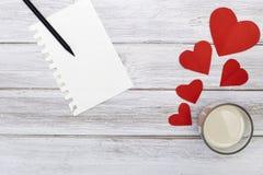 Papier rouge de coeurs du crayon deux de bloc-notes avec du lait Images stock
