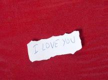 Papier sur le fond rouge avec le message de l'amour Photo libre de droits