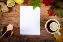 Papier, thé et miel sur la table avec des feuilles d'automne Photos stock