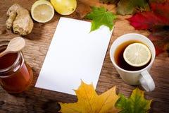 Papier, thé et miel sur la table avec des feuilles d'automne Images stock