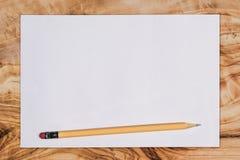 Papier und Bleistift auf einem hölzernen Schreibtisch, angesehen von oben genanntem mit Kopie s Lizenzfreies Stockbild