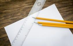 Papier und Bleistifte auf dem Holztisch Lizenzfreie Stockfotografie