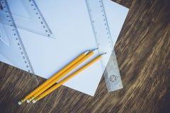 Papier und Bleistifte auf dem Holztisch Lizenzfreie Stockfotos