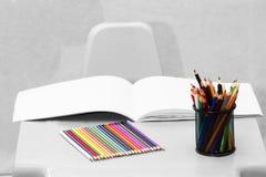 Papier- und bunte Bleistifte auf dem Tisch Lizenzfreie Stockfotografie