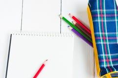 Papier- und bunte Bleistifte auf dem Tisch Ansicht von oben Lizenzfreie Stockbilder