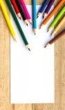 Papier- und Farbbleistifte auf Tabelle Lizenzfreie Stockfotografie