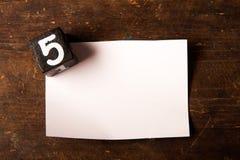 Papier- und hölzerner Würfel mit Zahl auf Holztisch, 5 Stockbilder