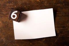 Papier- und hölzerner Würfel mit Zahl auf Holztisch, 6 Stockbilder