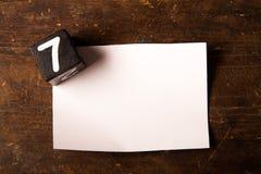Papier- und hölzerner Würfel mit Zahl auf Holztisch, 7 Lizenzfreies Stockbild