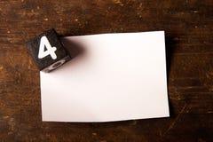 Papier- und hölzerner Würfel mit Zahl auf Holztisch, 4 Stockfotos