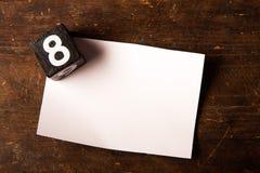 Papier- und hölzerner Würfel mit Zahl auf Holztisch, 8 Lizenzfreies Stockfoto