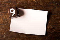 Papier- und hölzerner Würfel mit Zahl auf Holztisch, 9 Lizenzfreies Stockbild