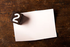 Papier- und hölzerner Würfel mit Zahl auf Holztisch, 2 Lizenzfreie Stockfotos