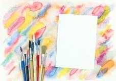 Papier vide avec des pinceaux au-dessus d'aquarelle diagonale colorée Image libre de droits