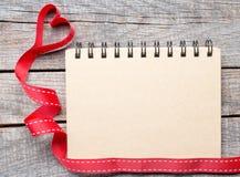 Papier vide de carnet avec le ruban de coeur Images stock