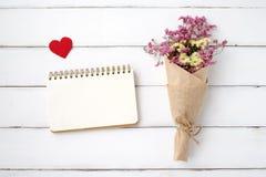 Papier vide de carnet, forme de coeur de tissu et bouquet de fleur dessus Photos stock