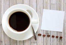 Papier z gorącą filiżanką i kawowymi fasolami zdjęcie stock
