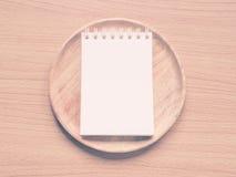 Papieranmerkung über hölzernen Teller, Konzept für Menü-Schaffung oder Restaurant-Kommentator, Stockfotos