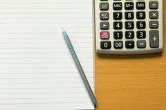 Papieranmerkung mit blauem Stift, Taschenrechner Lizenzfreie Stockfotografie