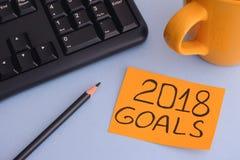 Papieranmerkung mit Schreiben 2018 Zielen auf einem Schreibtisch Stockfoto