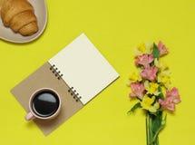 Papieranmerkungen über den gelben Hintergrund mit Blumen, Tasse Kaffee, Hörnchen lizenzfreies stockbild