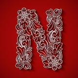 Papierausschnitt, weißer Buchstabe N Roter Hintergrund Blumenverzierung, Balinesetrachtenmode Lizenzfreie Stockfotos