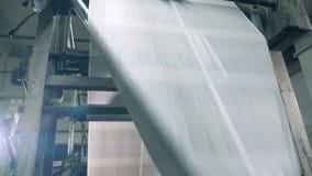 Papierbahn rollt entlang der industriellen Maschine stock footage