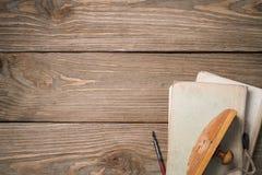Papierbeschwerer und alte Bücher auf einem Holztisch Stockbild