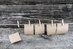 Papierblätter, die an einem Seil befestigt mit Clipn hängen stockfotos