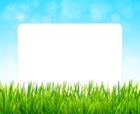Papierblatt auf Hintergrund mit grünem Gras und blauem Himmel Lizenzfreie Stockfotos